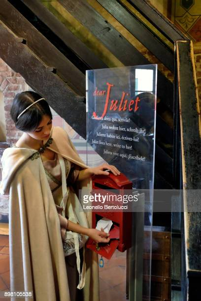"""An actress representing Juliet stands beside a letter box in which letters to Juliet are posted in Via Cappello 23 which is today known as """"Juliet's..."""