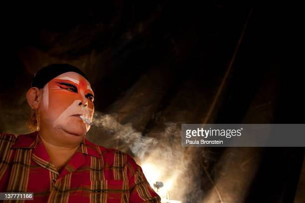 An actress with the Lao Yi Lai Heng Chinese opera orchestra smokes a cigarette backstage after a performance at the Plub Plachai temple on January 24...