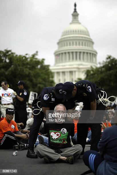 An ACTUP protester is arrested during a march through the streets surrounding the US Capitol 20 May 2004 in Washington DC Several hundred people with...
