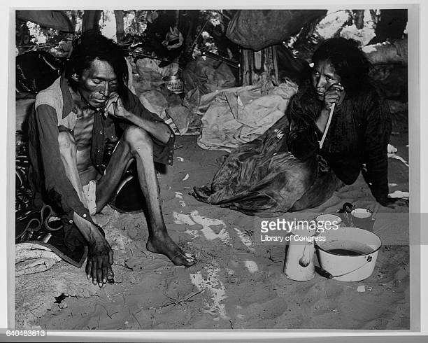 An acutely malnourished Navaho couple rests on the dirt inside a hut