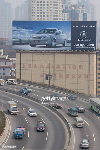 An ad for GM's Shanghai built Buick automobiles looms over a freeway in downtown Shanghai.