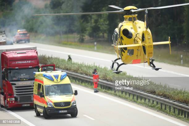 An ADAC helicopter lands next to the site where a truck caught fire following an accident on the A13 highway heading north on July 24 2017 near...