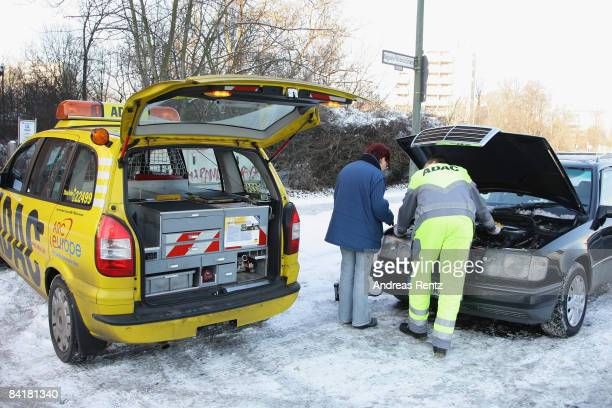 An ADAC technical assistant helps a woman with her broken down car on January 6 2009 in Berlin Germany Freezing conditions with snow ice and...