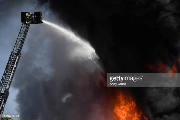 An Adams County firefighter gets up to the top of the ladder truck to try to get control of a fire in a large pile of crushed vehicles near 5600 York...