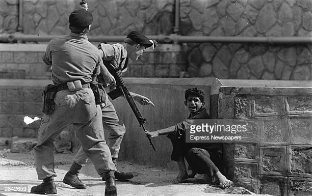 An Aden civilian crouching in terror as British soldiers threaten him during Arabian demonstrations in Crater