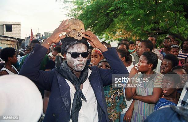 An adept of voodoo holds a human skull above his head while in trance as other followers look on 03 November 1998 during a ritual ceremony honoring...