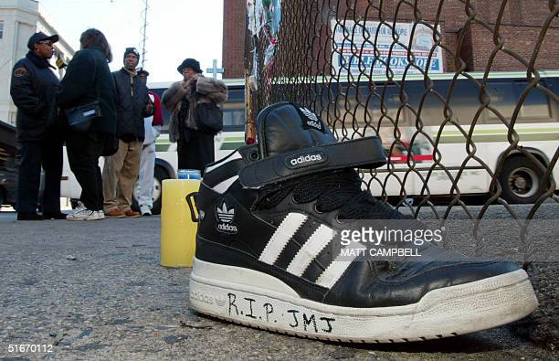 An Adidas sneaker bearing a mourner's message sits on the street outside a music studio in Queens New York 31 October 2002 where former Run DMC...