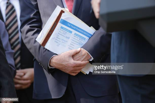 An administration official holds a document titled The Trump Playbook for the Future during a press conference to discuss a revised US trade...