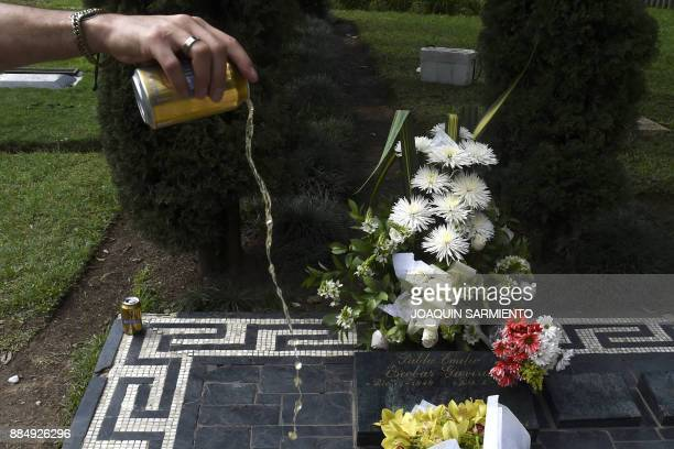 An admirer of druglord Pablo Escobar spills beer on his grave on the 24th anniversary of his death at the Montesacro cemetery in Itagui near Medellin...
