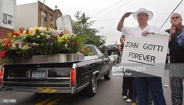 An admirer of legendary crime boss John Gotti salutes and holds a sign which reads John Gotti Forever as Gotti's funeral procession passes by the...