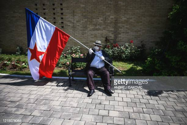 An admirer wearing a protective mask holds a Yugoslavia flag as he sits on a bench in front of the late former President of communist Yugoslavia...