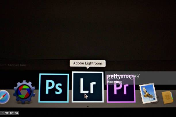 An Adobe Systems Inc Lightroom application shortcut is displayed between Photoshop left and Premiere Pro icons on a computer monitor in Tiskilwa...