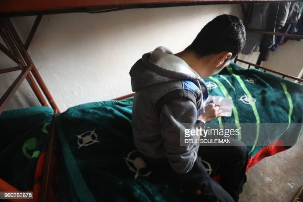 An adolescent boy makes objects from beads at the Hori rehabilitation centre for former Islamic State group child fighters run by Kurds in Tal...