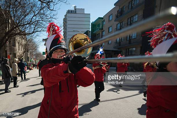 An adolescent boy trombonist in a winter coat plays his brass band instrument in a parade. The image was taken in strong sunlight. The image was...
