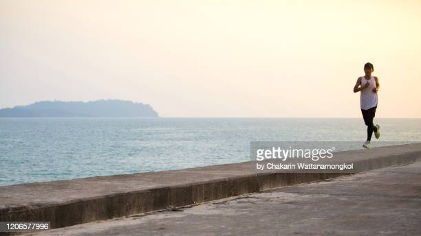 an adolescent man is running (jogging) by the sea at dusk. - 桟橋 ストックフォトと画像