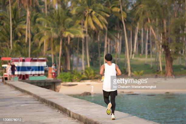 an adolescent man is running (jogging) by the sea. (ko kut - koh kood island) - hawaii flag stock pictures, royalty-free photos & images