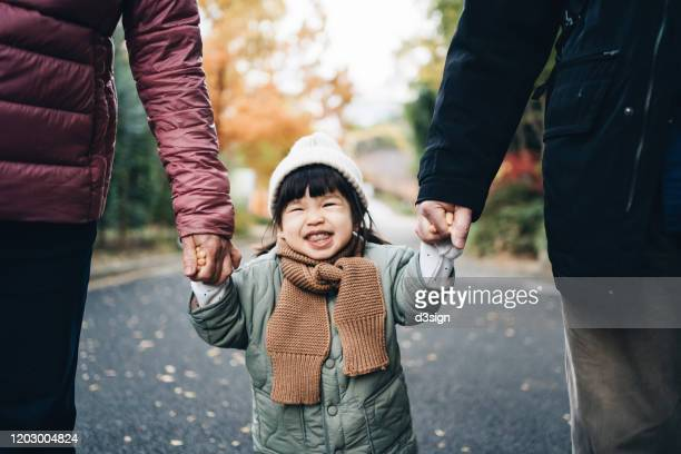 An adorable and happy little girl holding her grandparent's hand and having a relaxing walk in the park