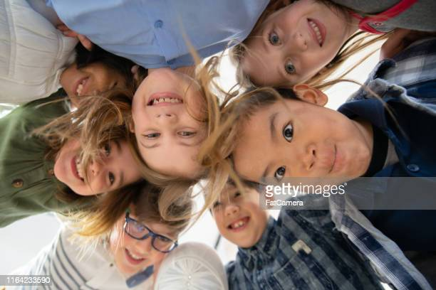 an adorable group of diverse kids look down at camera while huddled together - children only stock pictures, royalty-free photos & images