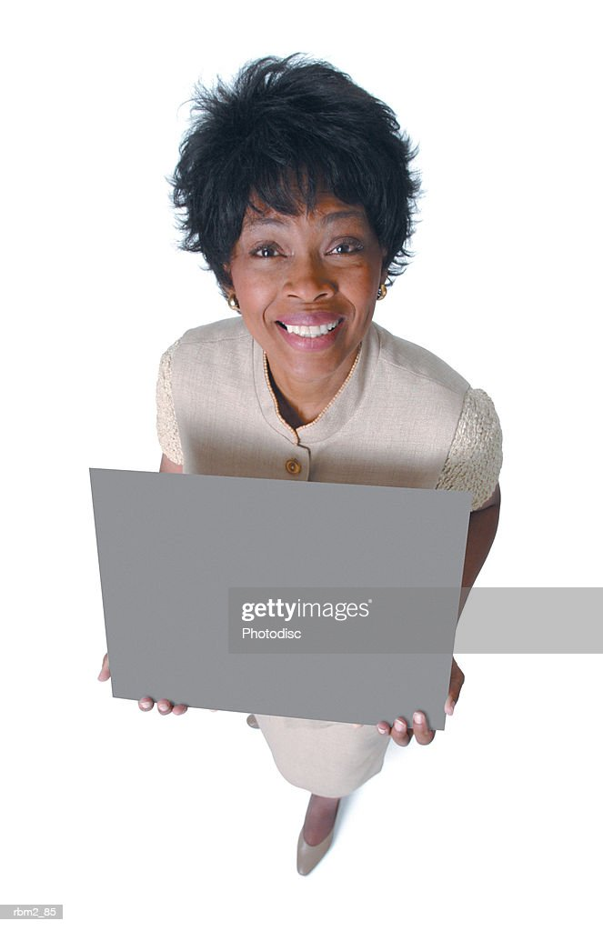 an adult african american woman in a tan dress holds a sign and smiles up at the camera : Stockfoto