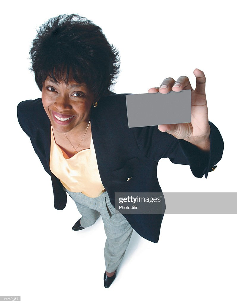 an adult african american woman in a yellow blouse and blue jacket holds up a  card and smiles : Stockfoto