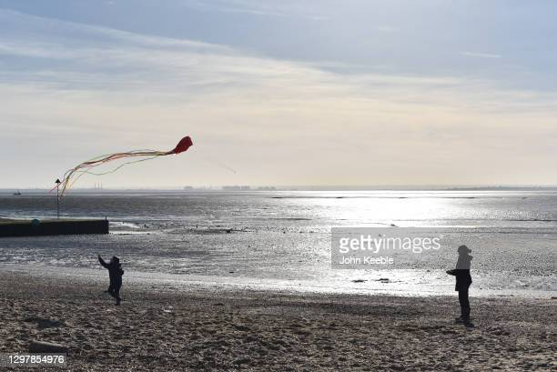 An adult and child fly a kite on Chalkwell Beach on January 22, 2021 in Leigh on Sea, England. United Kingdom. With a surge of covid-19 cases fueled...