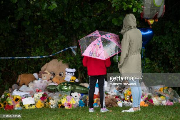 An adult and child look at floral tributes near the scene where the body of five-year-old Logan Williamson was found on August 2, 2021 in Sarn,...