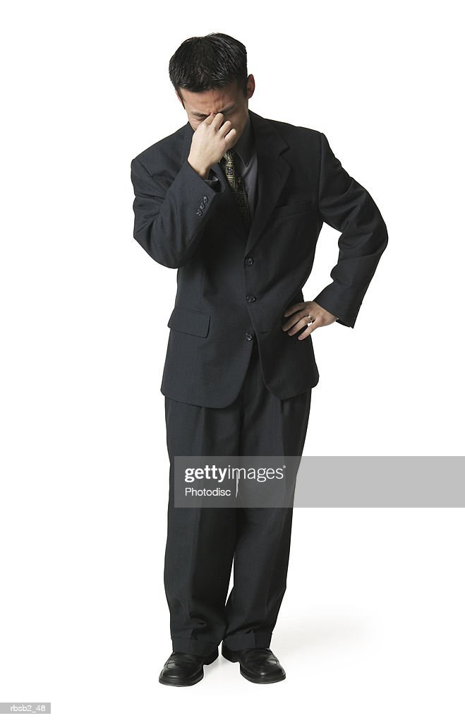 an adult asian business man in a dark suit burries his head in his hand as if overwhelmed : Foto de stock
