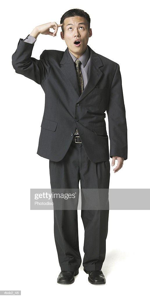 an adult asian business man in a dark suit ponts to his head and makes a funny face : Foto de stock