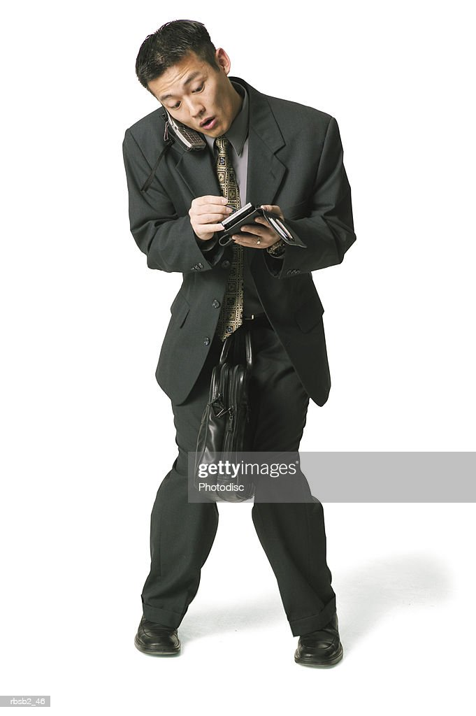 an adult asian business man in a dark suit tries to do too many things at once : Foto de stock