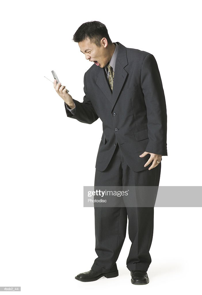 an adult asian business man in a dark suit yells angrily into his cell phone : Foto de stock