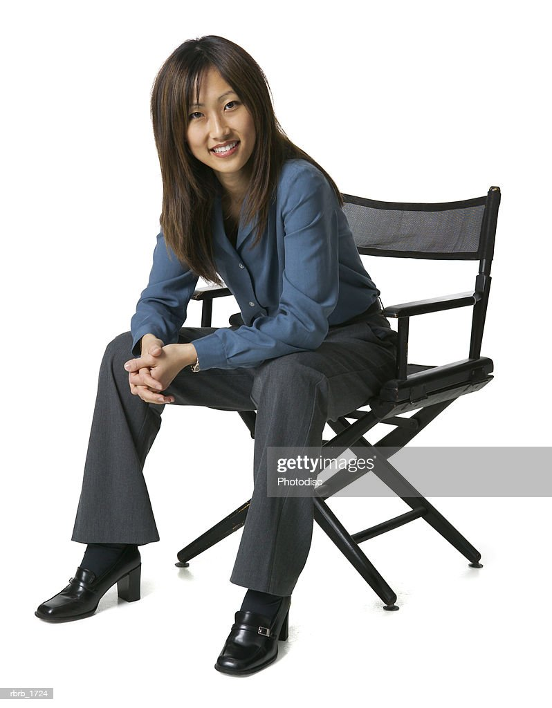 an adult asian business woman in grey pants and a blue shirt sits in a chair and smiles brightly : Stockfoto