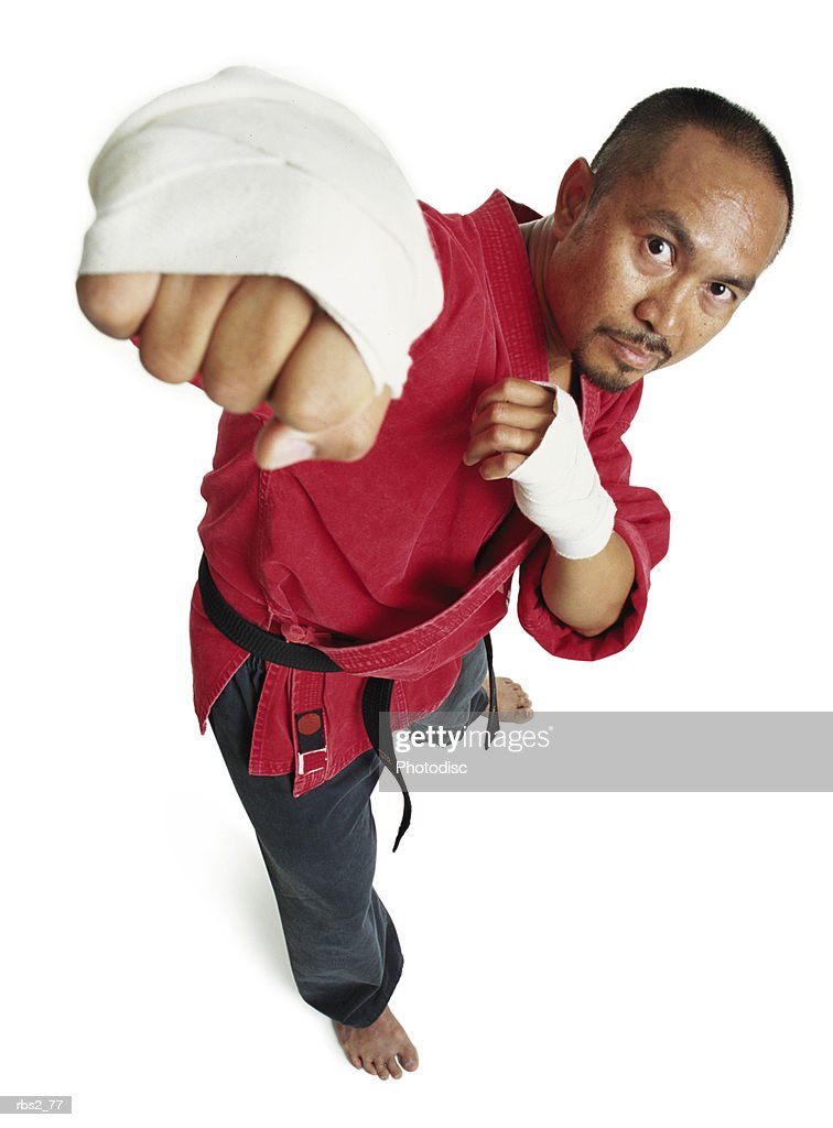 an adult asian male martial arts expert in red punches and looks up at the camera : Foto de stock