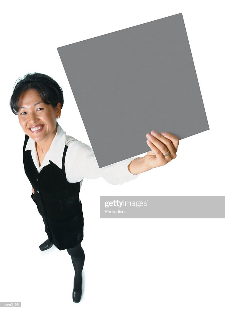 an adult asian woman in a black business outfit holds a sign up to the side as she smiles up into the camera : Stockfoto
