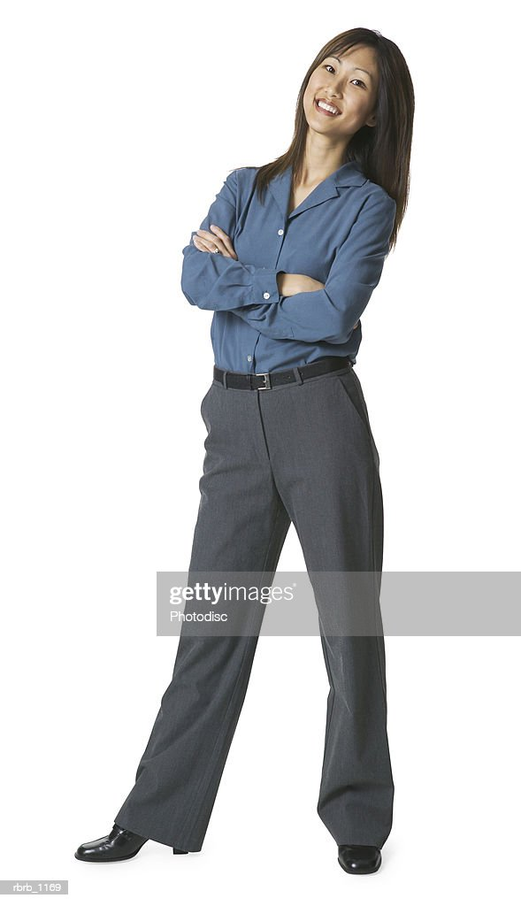 an adult asian woman in grey pants and a blue shirt folds her arms and smiles : Stockfoto