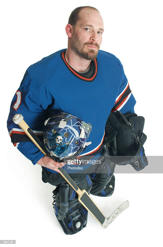 An adult bearded caucasian male hockey player holds his equipment and smiles smugly as he looks up at the camera : Foto de stock