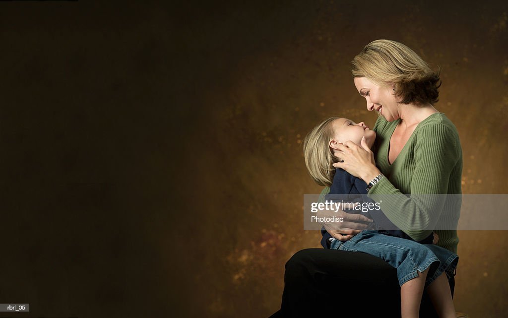 an adult blonde caucasian woman looks down at her young daughter on her lap : Foto de stock