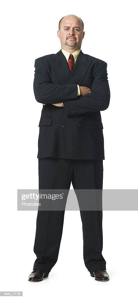 an adult caucasian business man in a suit folds his arms and smiles : Stockfoto