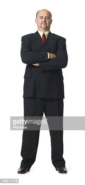 an adult caucasian business man in a suit folds his arms and smiles - compleet pak stockfoto's en -beelden
