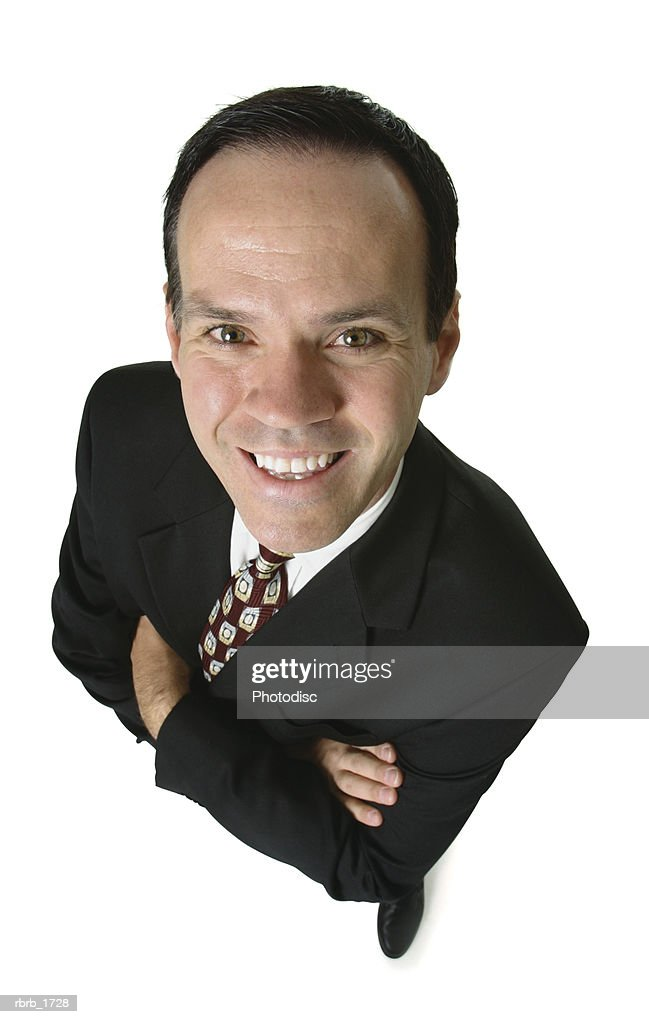 an adult caucasian business man in a suit folds his arms and smiles up at the camera : Stock Photo