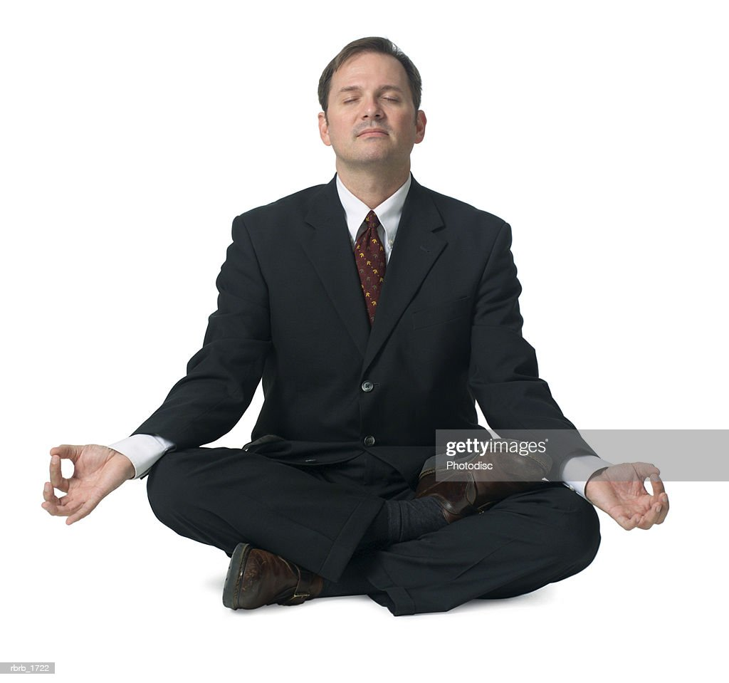 an adult caucasian business man in a suit sits down and meditates : Stockfoto