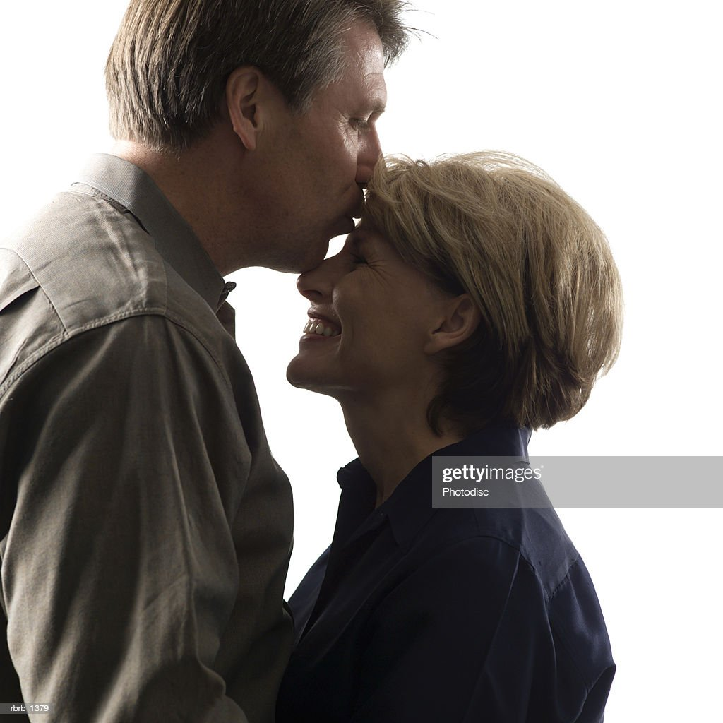 an adult caucasian couple embrace as the man leans in and kisses the woman on the forehead : Stockfoto