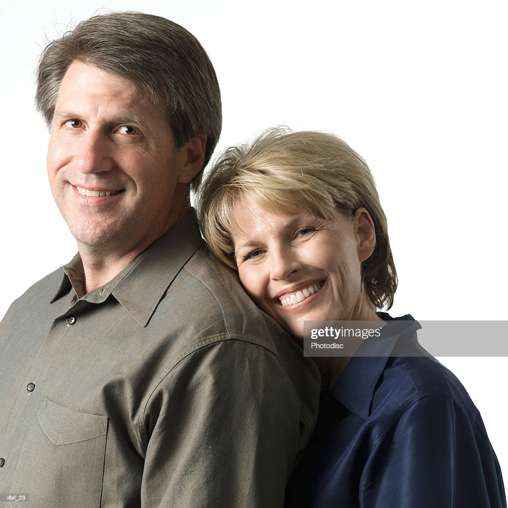 an adult caucasian couple smile as the woman rests her head on her husbands shoulder and smiles : Foto de stock