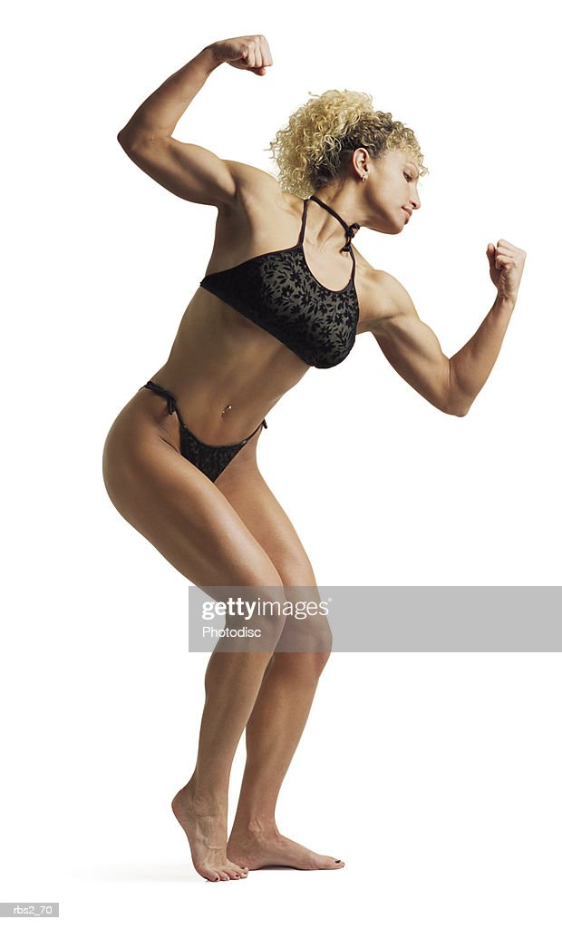 an adult caucasian female bodybuilder wearing a black bikini stands while flexing and posing for competition : Foto de stock