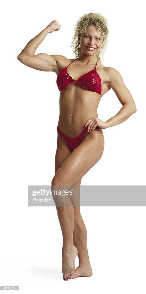 an adult caucasian female bodybuilder wearing a red bikini flexes and poses for competition : Foto de stock