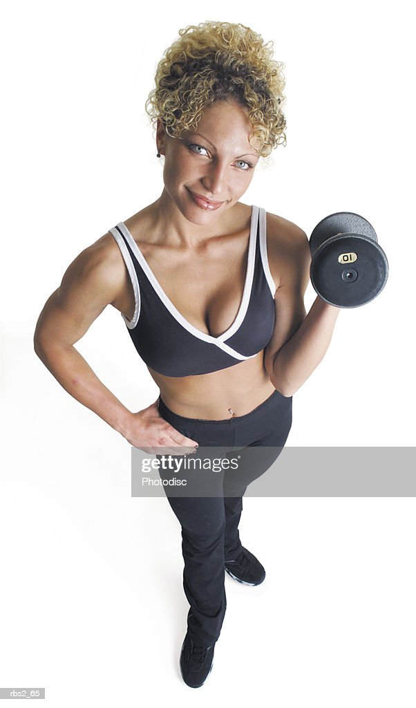 an adult caucasian female in a dark gray sports bra and pants stands with a dumbell raised smiling and looking up into the camera : Foto de stock
