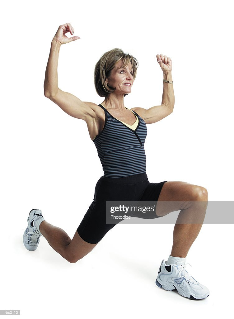 an adult caucasian female in a gray shirt and black shorts as she works out and does areobics : Foto de stock