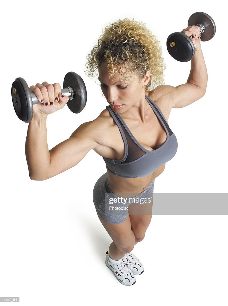 an adult caucasian female in grey shorts and sports bra works out by lifting dumbell weights up and above her head : Foto de stock