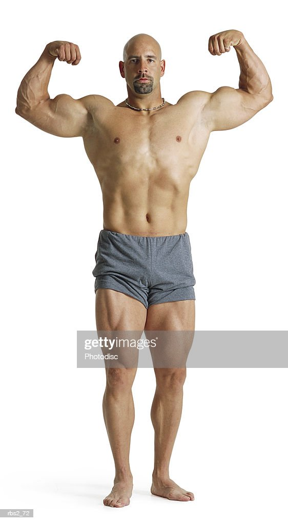 an adult caucasian male bodybuilder holds his arms up and flexes  his biceps and chest for competition : Stock Photo