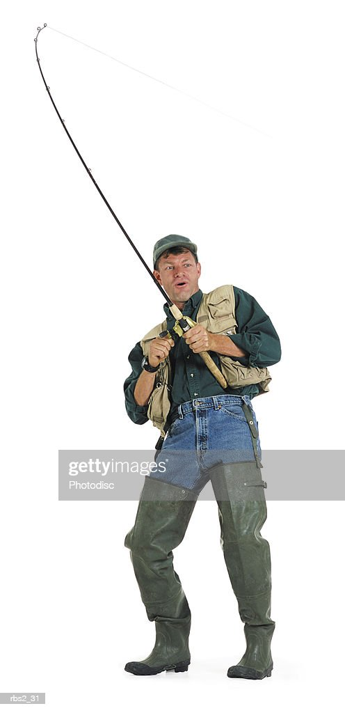 an adult caucasian male fisherman in a green shirt and fishing vest and waders pulls and reels in his line with his pole : Foto de stock