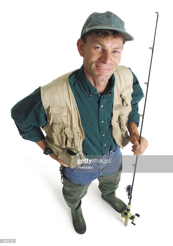 an adult caucasian male fisherman in a green shirt and tan fishing vest stands holding his pole and smiling as he looks up into the camera : Foto de stock
